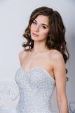 Schöne lächelnde Brautfrau mit dem langen gelockten Haar, das im Hochzeitskleid am Innenraum aufwirft Schönheitsinnenporträt Lizenzfreies Stockbild