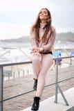 Schöne lächelnde Brunettefrau, die auf einem Zaun vor Stadtstrand sitzt, Kamera lächelt und betrachtet Lizenzfreie Stockfotos