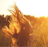 Schöne lächelnde Frau auf einem Gebiet bei Sonnenuntergang Weiblicher Kursteilnehmer mit Mantel Stockfotografie