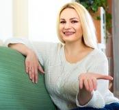 Schöne lächelnde Frau auf einem Sofa Lizenzfreie Stockfotos