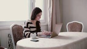 Schöne lächelnde Frau benutzt Laptop in einem hellen Speisen Lizenzfreie Stockfotos