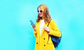 Schöne lächelnde Frau der Mode, die Smartphone verwendet stockbilder