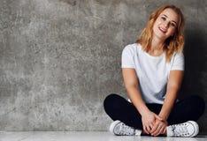 Schöne lächelnde Frau, die auf Boden gegen Betonmauer sitzt stockfotos