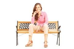 Schöne lächelnde Frau, die auf einer Bank sitzt und Kamera betrachtet Stockfotografie