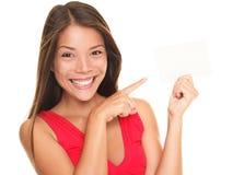 Schöne lächelnde Frau, die auf Geschenkkarte zeigt Lizenzfreie Stockfotos