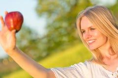 Schöne lächelnde Frau, die einen roten Apfel im Park isst Im Freiennatur lizenzfreies stockfoto