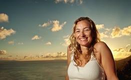 Schöne lächelnde Frau, die einen tropischen Sonnenuntergang genießt Lizenzfreies Stockfoto