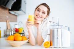 Schöne lächelnde Frau, die frischen Orangensaft trinkt Stockbilder