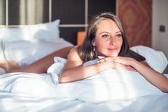 Schöne lächelnde Frau, die in ihrem Schlafzimmer liegt Stockbild