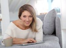 Schöne lächelnde Frau, die Tablette verwendet Lizenzfreie Stockbilder