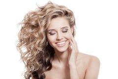 Schöne lächelnde Frau. Gesundes langes gelocktes Haar Stockbilder