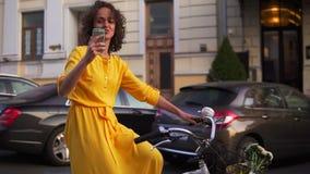 Schöne lächelnde Frau im langen gelben Kleid, das Stadtfahrrad mit einem Korb und Blumen inner fährt und mit filmt stock footage