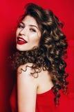 Schöne lächelnde Frau mit den roten Lippen im roten Kleid Stockbilder