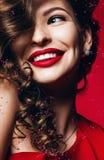 Schöne lächelnde Frau mit den roten Lippen und den Blumenblättern Lizenzfreie Stockfotos