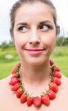 Schöne lächelnde Frau mit den roten Perlen gemacht von der frischen Erdbeere Stockfotos