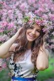 Schöne lächelnde Frau mit einem Kranz im blühenden Frühlingsgarten Stockbild