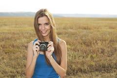 Schöne lächelnde Frau mit Kamera auf Natur lizenzfreie stockfotos