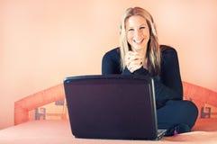 Schöne lächelnde Frau mit Kopfhörern und Laptop lizenzfreie stockbilder