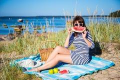 Schöne lächelnde Frau mit Scheibe der Wassermelone auf dem Strand Lizenzfreies Stockbild