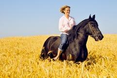 Schöne lächelnde Frau reitet Pferd Lizenzfreie Stockbilder