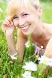 Schöne lächelnde Frau unter Frühlingsblumen Lizenzfreie Stockfotografie