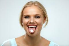 Schöne lächelnde Frau, welche die Medizin, Pille auf Zunge halten einnimmt stockbild