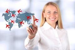 Schöne lächelnde Frau zeichnende Wege eines Flugzeuges auf Weltkarte lizenzfreie stockfotos