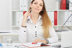 Schöne lächelnde Geschäftsfrau, die am Büroarbeitsplatz in camera schaut Porträt sitzt Lizenzfreie Stockfotografie