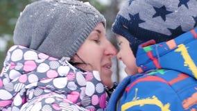 Schöne lächelnde Gesichtsnahaufnahme Eine glückliche Mutter küsst ein Kind gegen den Hintergrund eines schneebedeckten Waldes des stock video