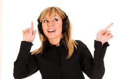 Schöne lächelnde hörende Musik der jungen Frau Stockbilder
