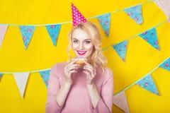 Schöne lächelnde junge Blondine mit einem Donut Feier und Partei lizenzfreies stockfoto