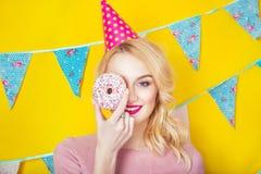 Schöne lächelnde junge Blondine mit einem Donut Feier und Partei lizenzfreies stockbild