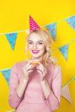 Schöne lächelnde junge Blondine mit einem Donut Feier und Partei stockbild
