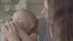 Schöne lächelnde junge Frau der Nahaufnahme, die ihr Baby von der kleinen Babyflasche in der Küche einzieht Konzept von a stock footage