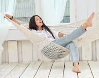 Schöne lächelnde junge Frau, die sich zu Hause in der Hängematte entspannt Stockfoto