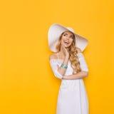 Schöne lächelnde junge Frau im weißem Kleid und in Sun-Hut schaut weg