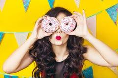 Schöne lächelnde junge Frau mit einem Donut Feier und Partei stockbilder