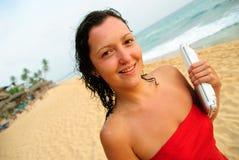 Schöne lächelnde junge Frau mit Laptop auf Strand Stockfotos