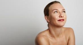 Schöne lächelnde junge Frau in weißem mit buntem Kranz auf Kopf Stockbilder