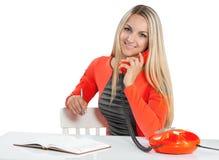 Schöne lächelnde junge Geschäftsfrau, die mit Telefon an spricht stockfotografie