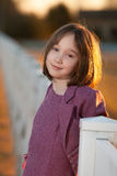 Schöne lächelnde junge Mädchen auf Zaun bei Sonnenuntergang Stockbild