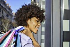 Schöne lächelnde junge schwarze Frau, die Einkaufstaschen auf ihrer Schulter hält Konzept über das Einkaufen, Lebensstil und peop lizenzfreie stockfotografie