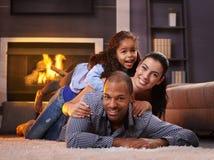 Schöne lächelnde Mischrennenfamilie zu Hause Lizenzfreie Stockbilder