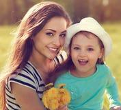 Schöne lächelnde Mutter, die ihre nette Tochter mit Gelb umfasst Lizenzfreies Stockfoto