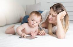 Schöne lächelnde Mutter und 10 Monate alte Baby, die auf Bett liegen Stockfotografie