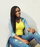 Schöne lächelnde tragende Jeans der afrikanischen Frau kleidet auf Treppe Stockfoto