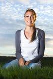 Schöne lachende junge Frau, die auf dem Gebiet sitzt Lizenzfreies Stockbild