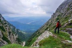 Schöne Landschaft in den Bergen und im Frauenbergsteiger, welche die Ansicht bewundern Stockbild