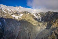 Schöne Landschaft des Neuseelands - Hügel bedeckt durch grünes Gras mit den mächtigen Bergen hinten bedeckt durch Schnee Stockbilder