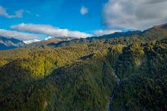 Schöne Landschaft des Neuseelands - Hügel bedeckt durch grünes Gras mit den mächtigen Bergen hinten bedeckt durch Schnee Stockfotografie